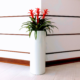 Flower arrangement in tall modern white cylinder planter